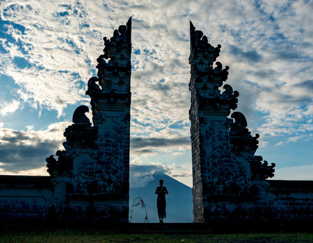 The silhouette of woman praying between split gateway wich is called candi bentar in the acient balinese temple Pura Luhur Lempuyang. Stratovolcano Gunung Agung in the cloudy dramatic sky on the background, Bali, Indonesia
