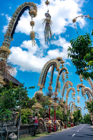 Traditional balinese penjors along the street of Bali, Indonesia. Tall bamboo poles with decoration are set in honour of hindu gods on religious festivals like Galungal, Kuningan. Stock Photo