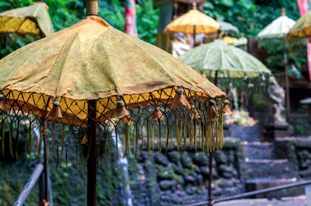 Yellow hindu umbrella in the outdoor shrine of Sebatu holy springs, Bali, Indonesia Фото со стока