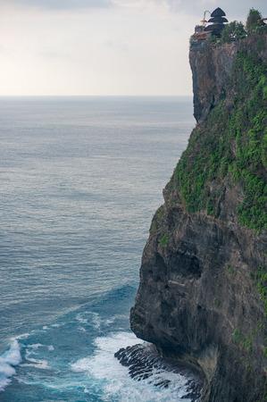 Hindu Uluwatu temple on the top of giant cliff in the ocean, Bali, Indonesia Фото со стока