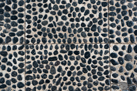 Tiled wall with mosaic of black pebbles