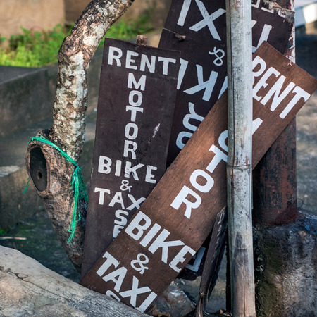 Stack of wooden banners with text - rent motor bike & taxi Фото со стока