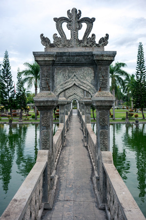 Ornate carved stone bridge over the pond in Taman Ujung park, Bali, Indonesia