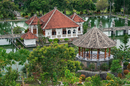 Alcove and water palace surrounded by green tropical foliage of Taman Ujung Royal park, Bali, Indonesia