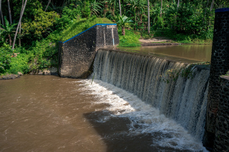Small hydroelectric dam on the river in tropical forest on Bali, Indonesia Фото со стока