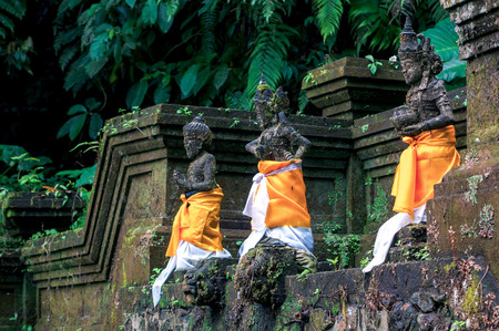 Stone hindu sculptures dressed in orange fabric sarongs. Architectural decor of holy springs in funeral complex Gunung Kawi near Ubud, Bali, Indonesia Фото со стока