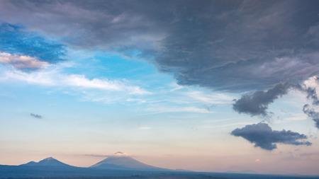 Beautiful balinese landscape - volcano Agung in cloudy sunset sky, Bali, Indonesia Фото со стока