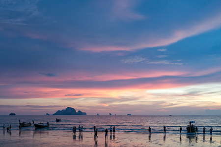 Tourists taking a picture of beautiful sunset on the Ao Nang beach in Krabi province, Thailand Фото со стока