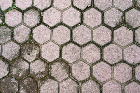 Fragment of old road paved by gray hexagonal tiles.