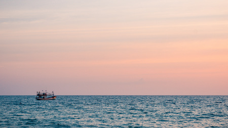 Lonely fishing boat in the sea during colorful tropical sunset, Krabi province, Thailand