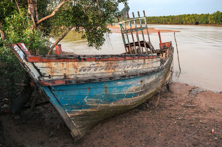 Old wooden boat aground on the river coast of Krabi town, Thailand