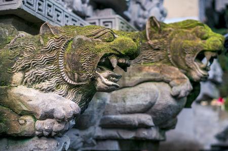 Old moss-grown statues of mythological animals - decoration of hindu temple Pura Gunung Lebah in Ubud town on Bali, Indonesia Фото со стока