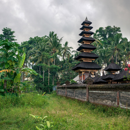 Traditional balinese roof Meru made from coconut fiber. This hindu temple is located on Tirta Tawar street in Ubud on Bali, Indonesia Фото со стока