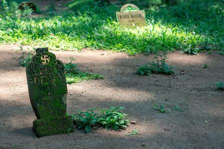 Swastika sign on moss-grown gravestone on the hindu cemetery in Ubud town on Bali, Indonesia Фото со стока