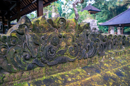 Decoration carved from the stone in traditional balinese style. Oriental decor in hindu temple Pura Gunung Lebah in Ubud town on Bali, Indonesia.