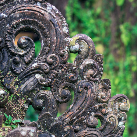 Ornate decoration carved from the stone on the green natural background Фото со стока