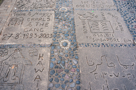 Pavement with lettering on the granite tiles imprinted by tourists in Ubud town, Bali, Indonesia