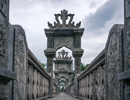 Ornate carved stone bridge in Taman Ujung park, Bali, Indonesia