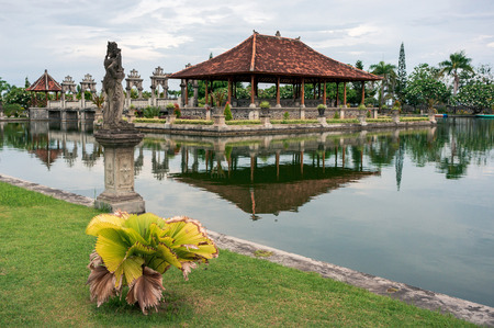 Pavilion with traditional balinese roof is reflected in a water in Taman Ujung park, Bali, Indonesia Фото со стока