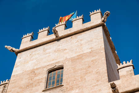 Valencian flag on top of historic building Lonja de la Seda in old town.