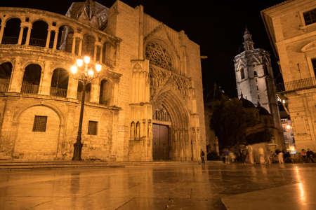 Valencia Cathedral on the Plaza de la Virgen at night. It is located in the historic center of Valencia.