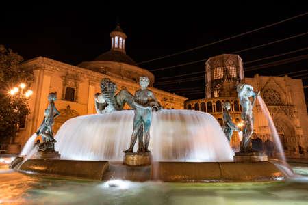 Valencia, Spain - 27.10.2019: Neptune fountain in night illumination. Fountain is located on the square Plaza de la Virgen in the historic center of Valencia.