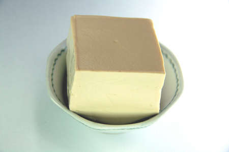 curd: soft pale food which has very little flavourbut is high in protein. Bean curd is made from soya bean.