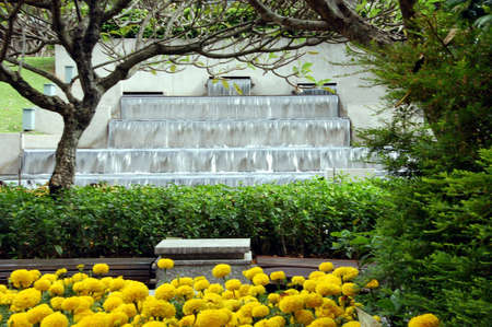 orifice: cascading waterfalls in publc park complete with flowers and benches