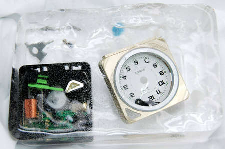 encapsulated: alarm clock breakway showing many plastic components  encapsulated in ice
