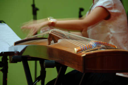 amplified: a musican playing  gu-jeng, an string musical instrument with  double string and flet