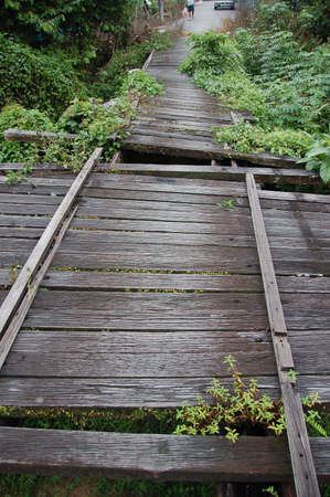 pit fall: broken wooden bridge showing missing planks and gaps Stock Photo