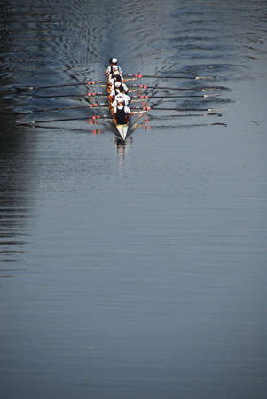 pratice: A rowing team pratice rowing in the evening on a smooth and calm river