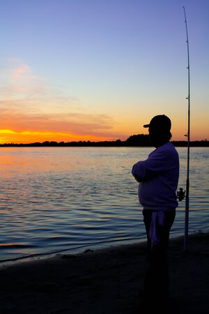 this is a photo of a man fishing down at the bay looking into the sunset.