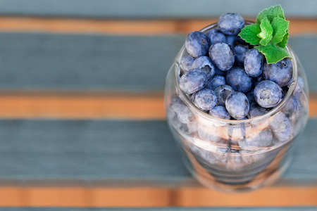 Berries blueberries lying on wooden deck in glass right side background Stock Photo