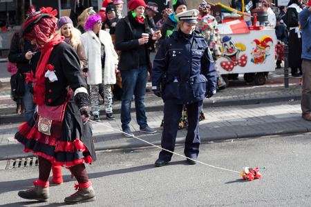 sonntag: Cologne, Germany - March 2nd, 2014  Carnival 2014  Female Police Officer looking at a toy on a carnival procession called  Schull- und Veedelszöch   Some spectators in the background, children inclusive  Editorial