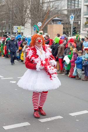 sonntag: Cologne, Germany - March 2nd, 2014  Carnival 2014  Women dressed as a clown at  carnival procession called  Schull- und Veedelszöch   Some spectators in the background, children inclusive