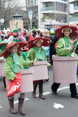 sonntag: Colonia, Alemania - 02 de marzo 2014 Carnaval 2014 Mujer con dos muchachas que usan custumes de flores en un desfile de carnaval llamado Schull- und Veedelsz�ch Algunos espectadores en el fondo, los ni�os inclusive Editorial
