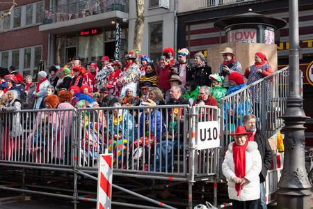 sonntag: Colonia, Alemania - 02 de marzo 2014 Carnaval 2014 espectadores de un desfile de carnaval que sienta en las gradas en el desfile de carnaval llamado Schull-und Veedelsz�ch Algunos espectadores en el fondo, los ni�os inclusive