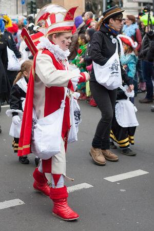 sonntag: Colonia, Alemania - 02 de marzo 2014 Carnaval 2014 Boy llevaba un disfraz de carnaval y paseos en un desfile de carnaval llamado Schull-und Veedelsz�ch Algunos espectadores en el fondo, los ni�os inclusive Editorial