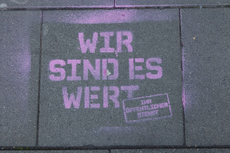 Cologne, Germany - March 27, 2014  Graffiti on the bottom meaning  we are worth it - your public service   This strike was organised by ver di  They are a large German trade union with 2 2 million members