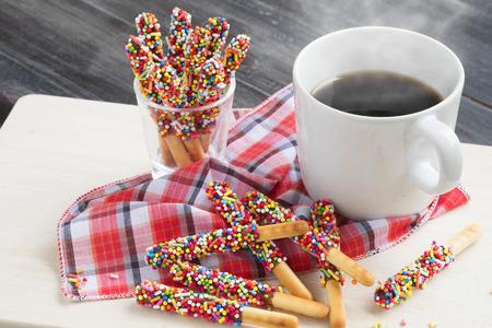 나무 배경에 뜨거운 커피와 함께 빼빼로 사탕. 스톡 콘텐츠