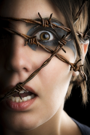 madness: Terrified woman with barbed wire around the head  Stock Photo