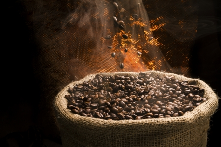 Sack full of still hot, freshly roasted coffee beans with the falling coffee beans
