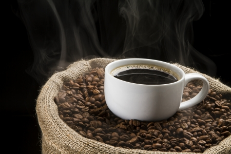 Sack full of still hot, freshly roasted coffee beans with the mug in the middle  Stock Photo