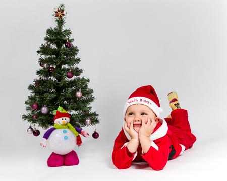 Dreaming baby boy dressed as Santa Claus lying next to Christmas tree. White .
