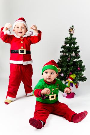 Two baby boys dressed as Santa Claus and Santas Helper next to Christmas tree. White background. Stock Photo