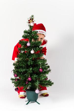 Baby boy dressed as Santa Claus hiding behind Christmas tree. Stock Photo