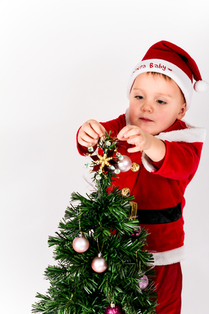 Baby boy dressed as Santa Claus putting the star on the top of Christmas tree. Decorating. White background.