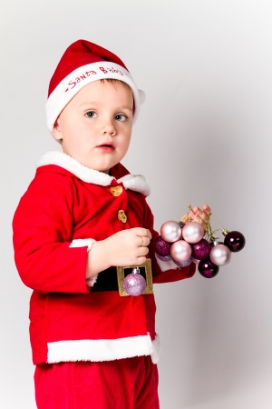 Baby boy dressed as Santa Claus holding Christmas baubles. White background. Stock Photo