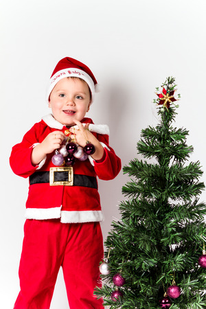 Baby boy dressed as Santa Claus decorating  Christmas tree, holding baubles.  photo